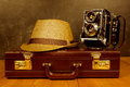 Vintage retro camera with fedora hat on an old briefcase Royalty Free Stock Photo