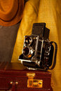 Vintage retro camera on old briefcase with old fashion clothing n the background Royalty Free Stock Image