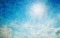 Vintage retro image of sunny blue sky with puffy clouds grunge and creased canvas texture Stock Image
