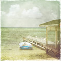 Vintage retro stylized photo of caribbean beach seascape with boats and clouds in the background Stock Photos