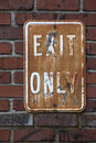 Vintage rusted exit only sign old dirty and rusty for hanging on old brick wall Royalty Free Stock Photo