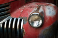 Vintage rusty red truck car with a new headlight, soft focus Royalty Free Stock Photo