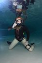 Vintage scuba woman with black neoprene dress diving underwater Royalty Free Stock Photos