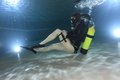 Vintage scuba woman with black neoprene dress diving underwater Royalty Free Stock Images