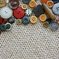 Vintage sewing buttons framing fabric background a natural colored collection a various are a square of woft woven tan Stock Photo
