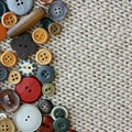 Vintage sewing buttons framing fabric background a natural colored collection a various are a square of woft woven tan Royalty Free Stock Photography