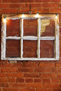 Vintage six pane window used as interior exterior decoration on red brick wall with string of accent lights Royalty Free Stock Images