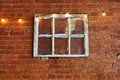 Vintage six pane window used as interior exterior decoration on red brick wall with string of accent lights Royalty Free Stock Photos