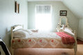 Vintage slanted ceiling bedroom well lighted with Stock Images