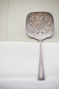 Vintage slotted spoon tarnished sitting on a white napkin Royalty Free Stock Photo