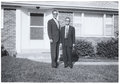 Vintage Snapshot: Tall man short man outside surburban house. Royalty Free Stock Photo