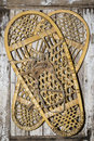 Vintage snow shoes on painted wood the retro snowshoe pair with rawhide lacing holds authentic leather bindings bear paw style Stock Photos