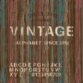 Vintage stamp alphabet and wooden background Royalty Free Stock Photo