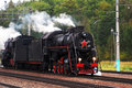 Vintage steam engine locomotive train moving down railroad autumn nature background Stock Photo