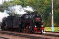 Vintage steam engine locomotive train moving down railroad autumn nature background Stock Photo