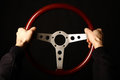 Vintage steering wheel detail of two hands holding a wooden on black Stock Photo