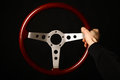 Vintage steering wheel a hand holding a wooden on black Stock Images