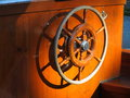 Vintage steering wheel inside boat a an old fixed on a wooden panel Stock Image