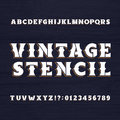 Vintage stencil typeface. Retro alphabet font on a wooden background.