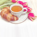 Vintage style breakfast tea and flowers croissant Stock Photos