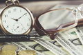 Vintage style finance concept with glasses, dollar bills, retro clock, coins and fountain pen. Selective focus Royalty Free Stock Photo