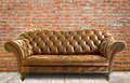 Vintage style  leather sofa with wooden floor and brick wall Royalty Free Stock Photo