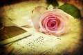 Vintage style picture of a pink rose on music notes textured old sheets Stock Images