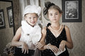 Vintage style portrait of children little girls try on a grandma s dress Stock Photo