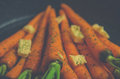 Vintage style rustic carrotts in a pan with butter image of carrots and herbs Royalty Free Stock Photo
