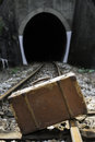 Vintage suitcase on railway road and tunnel Stock Photo