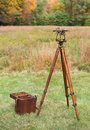 Vintage Surveyors Level (Transit, Theodolite) with wooden Tripod and Case in a field. Royalty Free Stock Photo