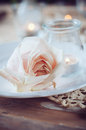 Vintage table setting with beige rose festive decoration candles and antique cutlery Stock Photography