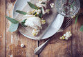 Vintage table setting with floral decorations napkins white roses leaves and berries on a wooden board background Royalty Free Stock Images