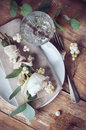 Vintage table setting with floral decorations napkins white roses leaves and berries on a wooden board background Stock Image