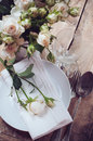 Vintage table setting with roses antique rustic dishes and cutlery on the wooden background close up Royalty Free Stock Image