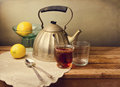 Vintage teapot with lemons and tea on wooden table Royalty Free Stock Photo