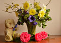 Vintage teddy bear and spring flowers a battered old next to Royalty Free Stock Photo