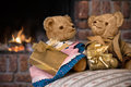 Vintage teddy bears in front of fireplace couple with christmas gifts Stock Image