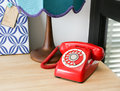 Vintage telephone red with rotary on wooden desk Royalty Free Stock Photos