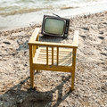 Vintage television on beach decor the lake shore chair and Royalty Free Stock Photos