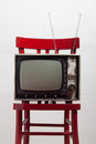 Vintage television on a red chair Royalty Free Stock Image