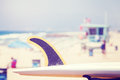 Vintage toned surfboard fin with lifeguard tower in distance. Royalty Free Stock Photo