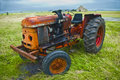 Vintage tractor on a field with a barn on the background Royalty Free Stock Photo