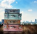 Vintage travel luggage on wooden with city view background Royalty Free Stock Photo