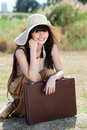 Vintage travel vertical portrait of a girl with a suitcase outside Royalty Free Stock Photo