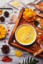 Vintage tray with warm autumn pumpkin soup decorated seeds and thyme in white bowl on rustic wooden table top view. Royalty Free Stock Photo