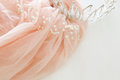 Vintage tulle pink chiffon dress and diamond tiara on wooden white table. Wedding and girl& x27;s party concept