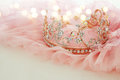 Vintage tulle pink chiffon dress and diamond tiara on wooden white table. Wedding and girl& x27;s party concept Royalty Free Stock Photo
