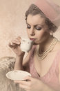 Vintage twenties woman attractive s lady with flapper dress and matching hat drinking tea Stock Photo