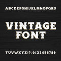 Vintage typeface. Retro distressed alphabet font on a wooden background.